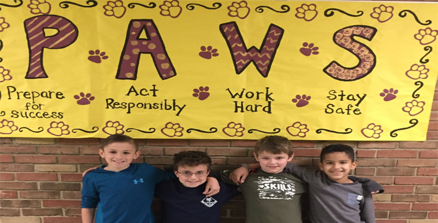kids smiling in front of PAWS sign